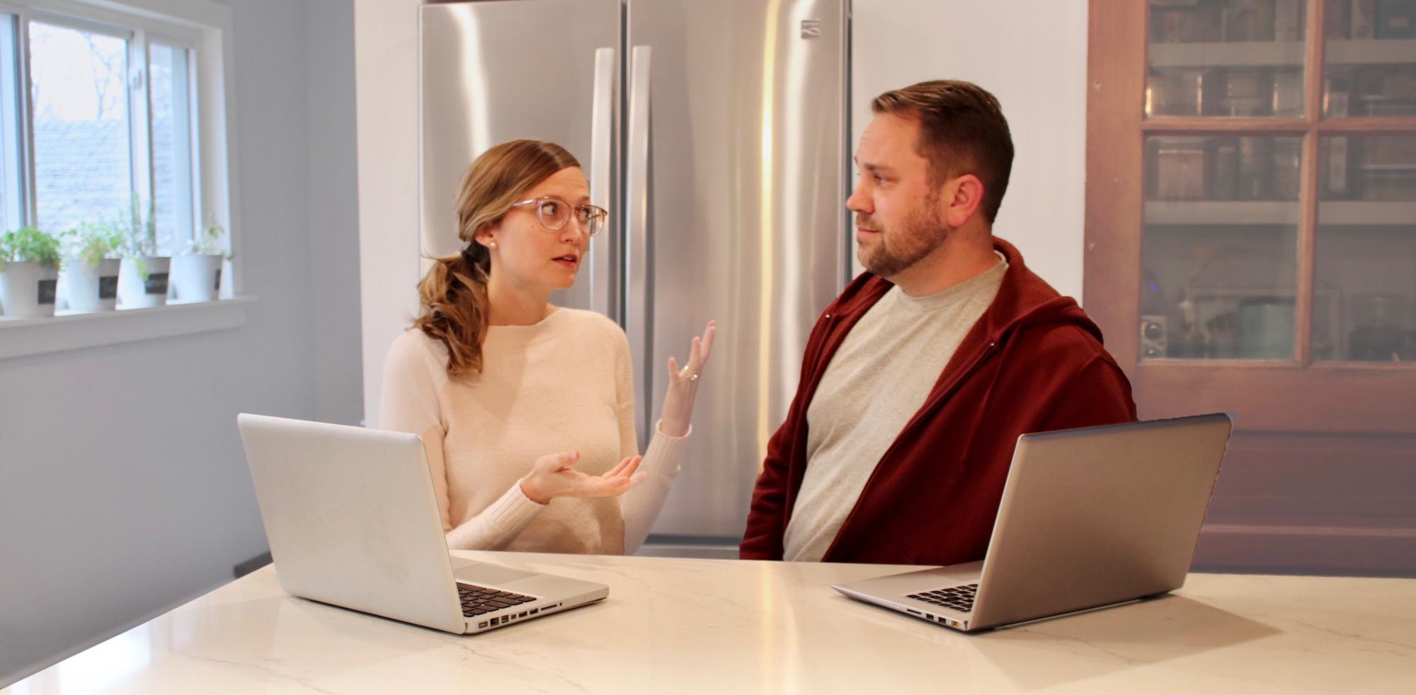 Picture of two people having a conversation in front of their computers.
