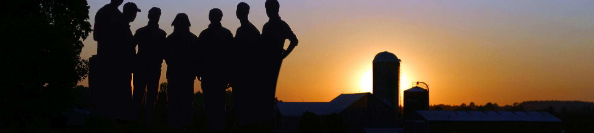 Image showing a group of individuals standing in the field with a barn and sunset in the background