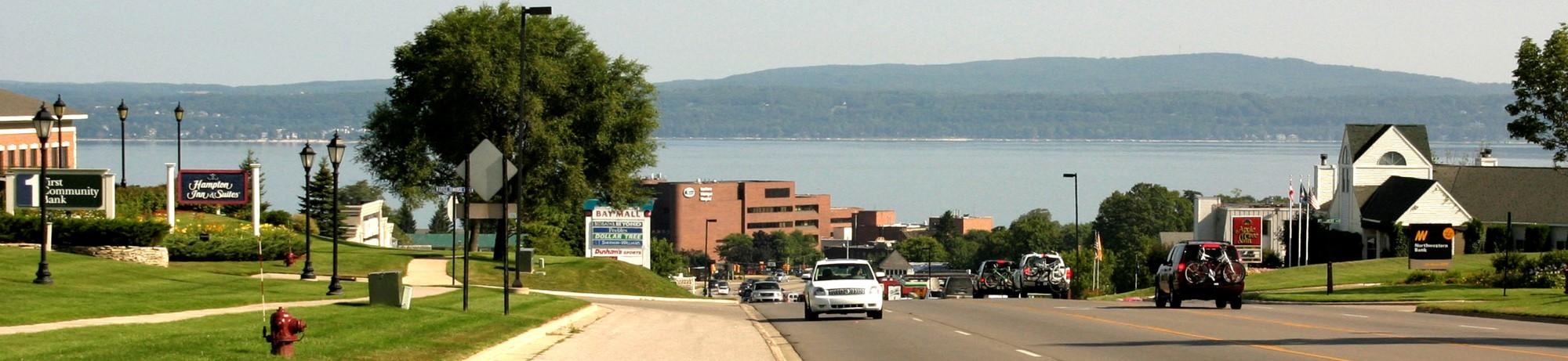 Image of highway overlooking Petoskey with monument signs on both sides.
